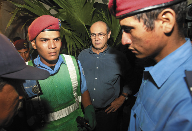 Nicaraguan journalist Carlos Fernando Chamorro (center), a vocal critic of President Daniel Ortega and the ruling Sandinista Party, with police at the Managua offices of CINCO, the nonprofit journalism organization Chamorro directs, October 10, 2008. In a continuing crackdown against Ortega's critics, the police returned the next day and raided CINCO's offices on trumped-up charges of money laundering.