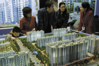 Prospective buyers looking at a model of a residential housing project at the Beijing Real Estate Fair, April 3, 2006