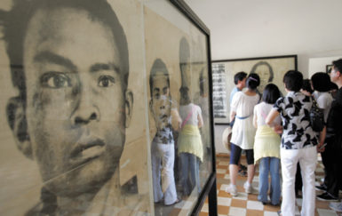 Tourists looking at photographs of Khmer Rouge victims at the Tuol Sleng Genocide Museum, Phnom Penh, Cambodia, February 13, 2009