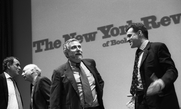 Paul Krugman and Niall Ferguson at the symposium; in the background are Nouriel Roubini and Jeff Madrick