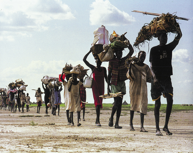 Internally displaced Sudanese returning to their village after having fled fighting in the Western Upper Nile region of southern Sudan, 2002; photograph by Sven Torfinn from Darfur: Twenty Years of War and Genocide in Sudan, edited by Leora Kahn and published by powerHouse Books