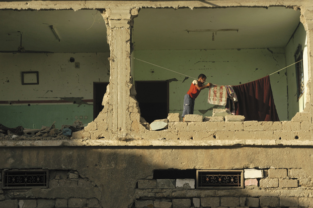 A Palestinian boy hanging laundry in a house damaged by Israel's bombardments of Gaza in January, Rafah refugee camp, Gaza Strip, July 2, 2009