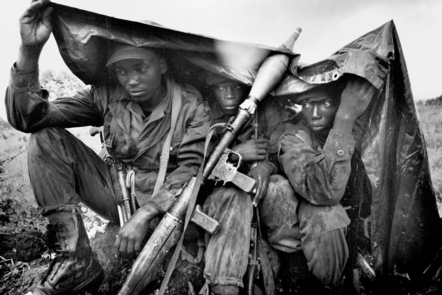 Government troops sheltering from the rain after a night of battles against rebel forces led by the warlord Laurent Nkunda, near Goma, eastern Congo, November 12, 2008; photograph by Marcus Bleasdale from The Rape of a Nation, a collection of his i