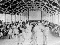 A dance hall in Fordlandia, Brazil, with a movie screen on the back wall; photographs from Greg Grandin's <i>Fordlandia: The Rise and Fall of Henry Ford's Forgotten Jungle City</i>