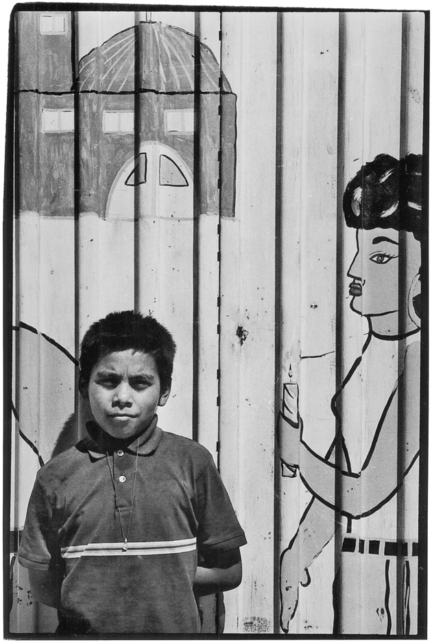 Boy and painted border fence, Colonia Chorizo, Mexicali, 2001; photographs by William T. Vollmann from the powerHouse edition of Imperial