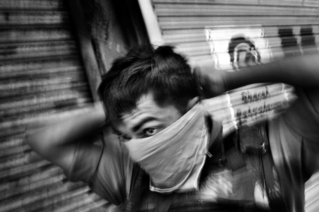 A member of the Indian Central Reserve Police Force protecting himself against tear gas during riots in Srinagar, the summer capital of Kashmir, July 16, 2009