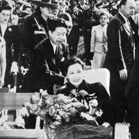 Madame Chiang at a celebration held in her honor at the Hollywood Bowl, April 4, 1943. The flowers she is holding were given to her by Mary Pickford, who can be seen in the background on the right.