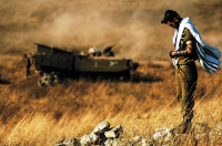 A photograph released by the Israel Defense Forces showing a religious Israeli soldier praying in a field