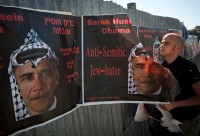 An Israeli man tearing anti-Obama posters hung by an extremist right-wing group, Jerusalem, June 14, 2009