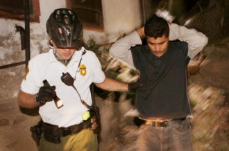 A US Customs and Border Protection agent apprehending an undocumented immigrant after he was spotted entering the country illegally, Nogales, Arizona, June 2, 2010
