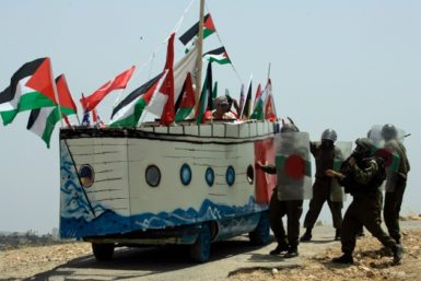 Israeli soldiers trying to stop a model of the Mavi Marmara during a protest against Israel's separation barrier, Bil'in, near Ramallah, June 4, 2010