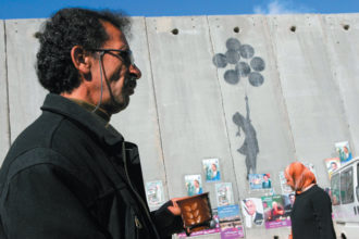 A Palestinian taxi driver waiting for passengers near the Qalandia checkpoint between Jerusalem and Ramallah, January 2006. In the background is the separation wall, with a graffiti painting by the British street artist Banksy and posters for the 2006 Pal