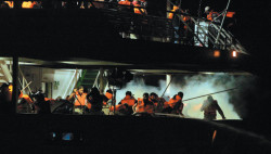 """Tear gas fired from Israeli assault ships surrounding passengers on the second deck of the <i>Mavi Marmara</i>, one of six vessels in the """"Freedom Flotilla,"""" which was intercepted by the Israeli military while trying to bring humanitarian supplies to"""