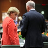 German Chancellor Angela Merkel speaks with Greek Prime Minister George Papandreou at an EU summit in Brussels, June 17, 2010