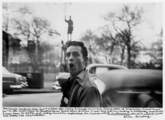 """Jack Kerouac; photograph by Allen Ginsberg, 1953. Ginsberg's caption reads: 'Jack Kerouac wandering along East 7th Street after visiting Burroughs at our pad, passing statue of Congressman Samuel """"Sunset"""" Cox, """"The Letter-Carrier's Friend"""" in Tompkins Square toward corner of Avenue A, Lower East Side; he's making a Dostoyevsky mad-face or Russian basso be-bop Om, first walking around the neighborhood, then involved with The Subterraneans, pencils & notebook in wool shirt-pockets, Fall 1953, Manhattan."""""""