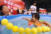 Chinese parents urging their babies on during a swimming contest, Beijing, September 20, 2009
