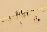 Villagers wave to a Pakistan Navy helicopter approaching a flooded area, Ghaus Pur, near Sukkur, Sindh province, August 11, 2010