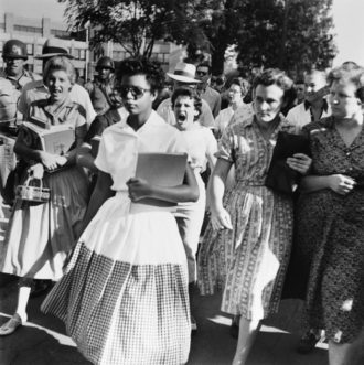 Elizabeth Eckford, one of the Little Rock Nine—a group of African-American students enrolled in the segregated Little Rock Central High School following the Brown decision—pursued by a mob on the first day of the school year, September 4, 1957. Arkansas National Guardsmen sent by Governor Orville Faubus blocked the nine from entering the school; three weeks later President Eisenhower sent federal troops to protect them and enforce desegregation.