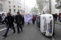 Demonstrators walking past a damaged car as they protest against France's government pensions reform, Lyon, October 18, 2010
