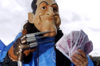 A protester wearing a mask representing French president Nicolas Sarkozy and fanning euro notes during a demonstration, Paris, October 19, 2010