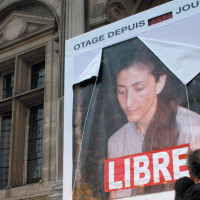 Freed hostage Ingrid Betancourt removing a portrait of herself from the Hôtel de Ville in Paris the day she returned to France, July 4, 2008