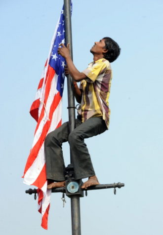 A worker removes the US and Indian national flags after the departure of US President Barack Obama and his wife Michelle from New Delhi, November 9, 2010