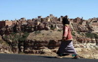A Yemeni woman walking on the main road leading to the mountain village of Kawkaban, north of the capital Sanaa, January 10, 2010