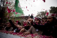 Supporters of Pakistani religious party Sunni Tehreek chanting slogans in favor of Mumtaz Qadri, alleged killer of Salman Taseer, and throwing rose petals while waiting for him outside an Anti-Terrorist Court in Rawalpindi, Pakistan, January 6, 2011