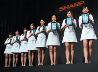 Models showing off Sharp's new Galapagos e-book readers at a news conference in Tokyo, September 2010