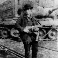 József Tibor Fejes, a young Hungarian identified by C. J. Chivers in The Gun as 'the first known insurgent to carry an AK-47.' According to Chivers, 'Fejes obtained his prize after Soviet soldiers dropped their rifles during their attack on revolutionaries in Budapest in 1956.... The Hungarian Revolution marked the AK-47's true battlefield debut.'