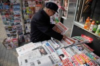 A Chinese newsstand with a newspaper in the foreground headlined,