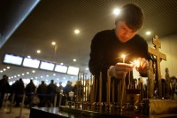 A clergyman lighting candles at the site of a bombing at Domodedovo Airport, January 26, 2011