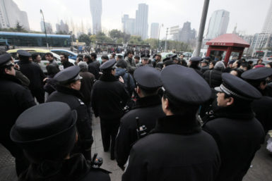 Chinese Police officers urge people to leave as they gather outside a cinema for a planned pro-democracy protest, Shanghai, China, Sunday, February 20, 2011