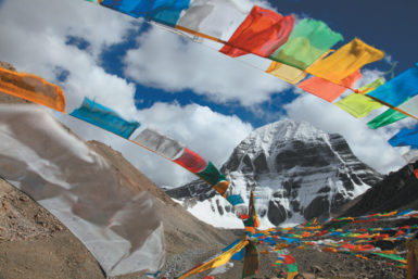 Buddhist prayer flags at the base of Mount Kailas in Tibet, where pilgrims come to walk the perimeter of the mountain, and where some monks and nomads follow the practice of sky burial. 'Especially in this propitious month of Saga Dawa,' Colin Thubron writes, 'people may repair to lie down and enact their own passing.'