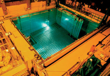 A storage pool for spent nuclear fuel. The blue color is caused by Cerenkov radation, produced when electrons from the radioactive decay are moving faster than the speed of light in water.