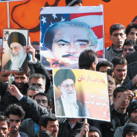 Iranian government supporters carrying posters of opposition leader Mir Hossein Moussavi (depicted in front of an American flag to imply that he is supported by the US) and Supreme Leader Ali Khamenei at a demonstration in Tehran, February 18, 2011