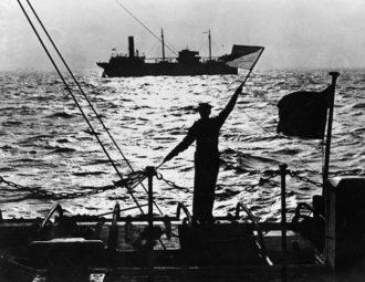 A British sailor signaling a merchant ship as it passes the naval control base in the Thames estuary, November 1939