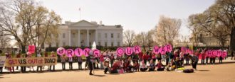 Protesters from the group Code Pink in front of the White House. Their umbrellas spell