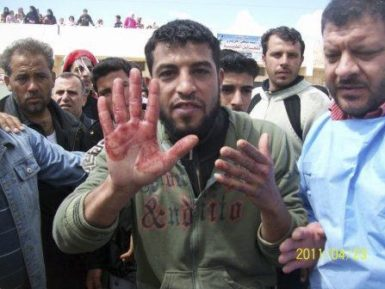 An anti-government protester holding up a bloodied hand during a funeral procession for slain activists in Izraa, Syria, Saturday, April 23, 2011. The image was taken on a mobile phone by a citizen journalist.