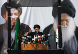The Iraqi Shiite cleric Moqtada al-Sadr giving a speech in Najaf during his first public appearance in Iraq after four years in exile in the Iranian city of Qom, January 8, 2011. Pictured on the banner behind him are his father-in-law, the late Grand Ayatollah Mohammed Baqir al-Sadr, founder of the Islamic Dawa Party, and his father, the late Grand Ayatollah Mohammed Sadiq al-Sadr. These two men are seen as the spiritual forebears of the Sadrist movement that Moqtada al-Sadr heads.