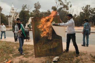 Young men burning a portrait of Muammar Qaddafi, Benghazi, Libya, March 21, 2011