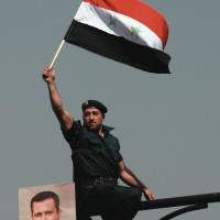 A Syrian soldier waving a flag at a rally in support of President Bashar al-Assad, Damascus, March 29, 2011