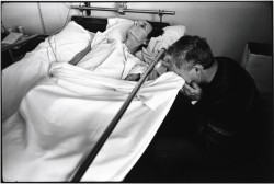 Joe is stricken with grief when visiting Bill. He cries into the bed sheet to keep Bill from seeing him. Hospice of Marin County, 1982