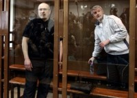 Mikhail Khodorkovsky and Platon Lebedev standing behind a glass wall in a Moscow courtroom, May 17, 2011