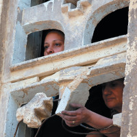 Coptic Christian women looking out from inside the Virgin Mary Church in the Imbaba neighborhood of Cairo, May 8, 2011. The church was set on fire during clashes between Christians and Muslims the previous night.