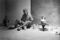 Paul Bowles making mint tea at a friend's house in the Medina of Marrakech, 1961; photograph by Allen Ginsberg