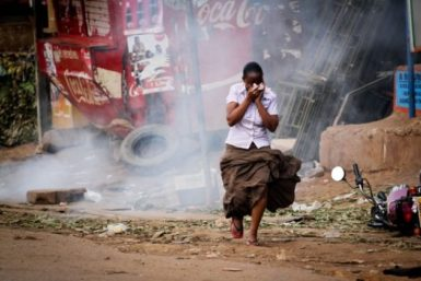 A woman running away from tear gas that was used by Ugandan authorities to disperse well wishers welcoming opposition leader Kizza Besigye back to Uganda, May 12, 2011