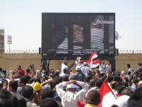 The crowd outside Egypt's Police Academy watching Mubarak's trial on a large-screen television