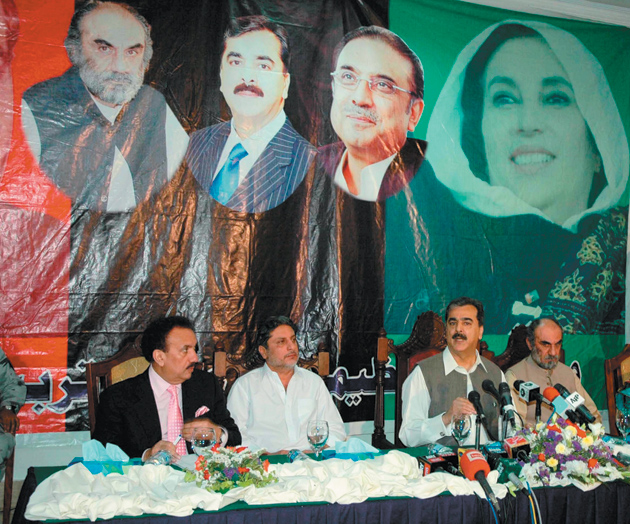 Pakistani Prime Minister Yousuf Raza Gilani, seated second from right, voicing concern about cuts in US aid at a press conference in Quetta, Balochistan, July 13, 2011. Seated with him are Pakistan's interior minister Rehman Malik (far left) and Balochistan's chief -minister Aslam Raisani (far right); above them hang portraits of Raisani, Gilani, President Asif Ali Zardari, and Benazir Bhutto.