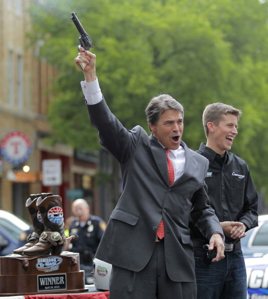 Texas Governor Rick Perry fires a gun filled with blanks at an event in downtown Fort Worth to kick off a weekend of NASCAR racing at the Texas Motor Speedway, April 15, 2010